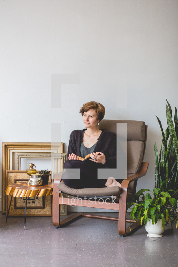 a woman sitting in a chair reading a book