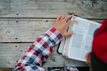 man reading a Bible outdoors at a picnic table