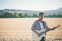 man playing a guitar outdoors