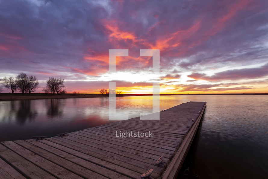 pier over calm water at sunset under a pink sky