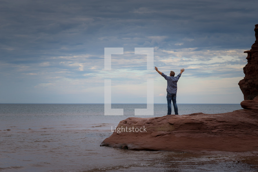 a man with raised arms on a beach