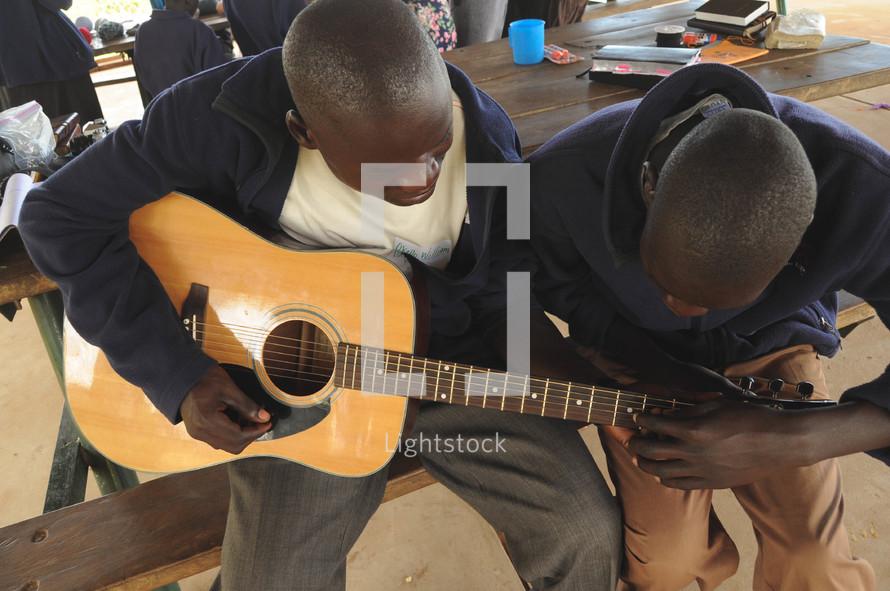 Man teaching a boy to play guitar.