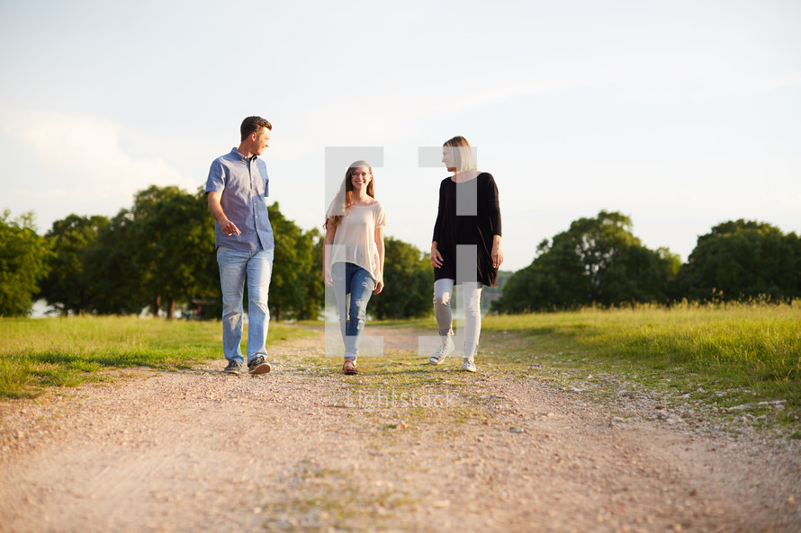 a mother and father walking and talking with their teenage daughter