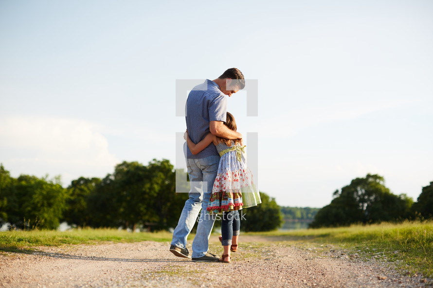a father and daughter hugging on a dirt road