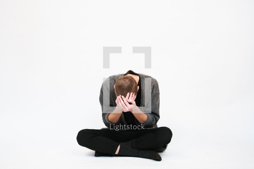 a man sitting holding his head down