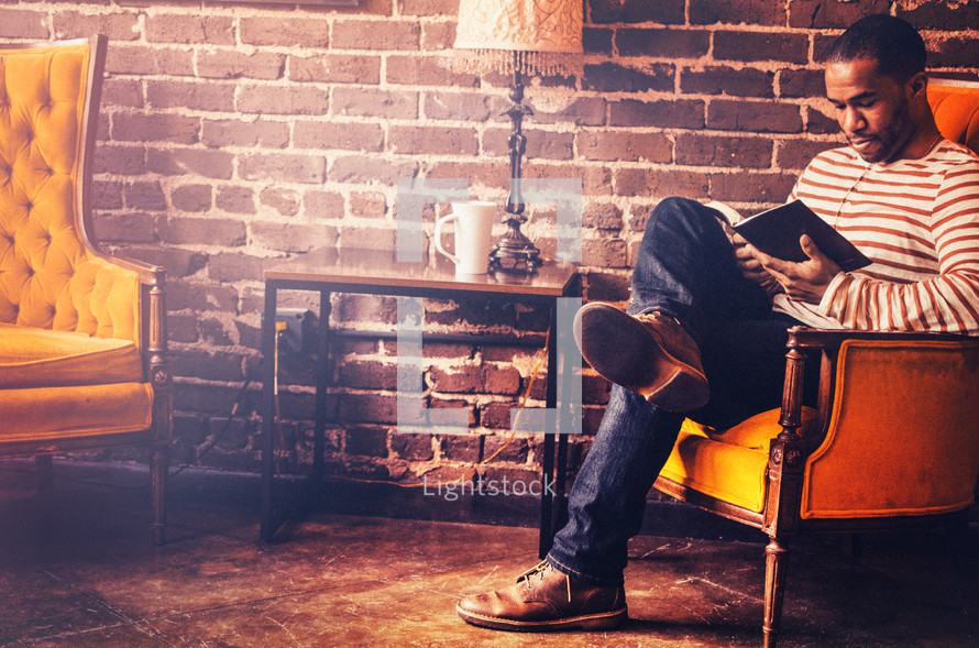 man reading a Bible sitting on a couch