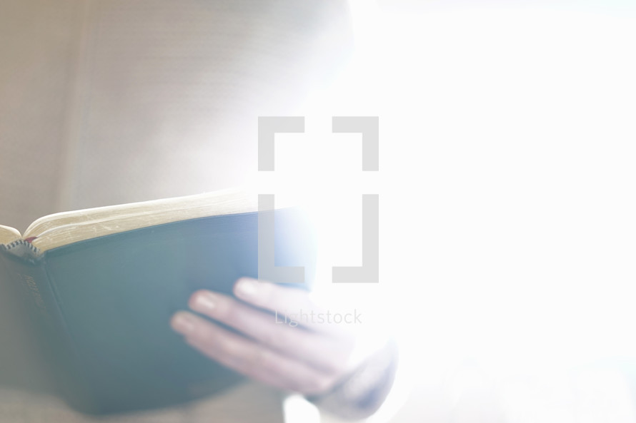reading a Bible in glowing light