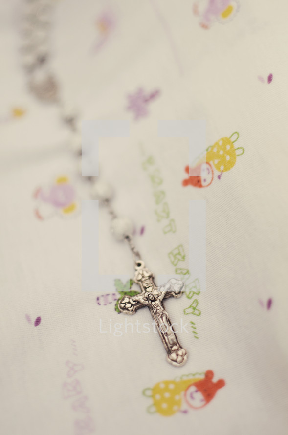 A cross necklace on a child's bedding.