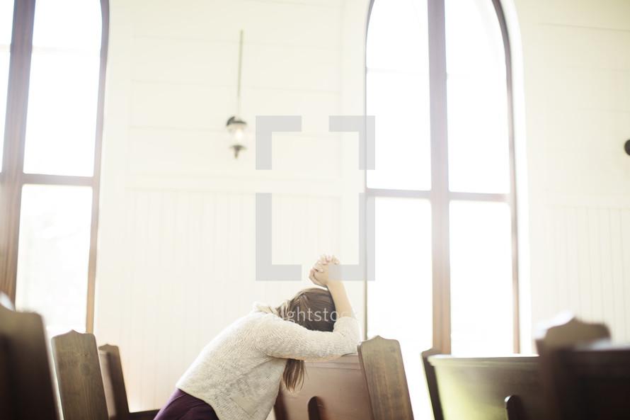 a woman praying sitting in a church pew
