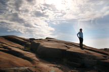 a man standing on a rocky slope