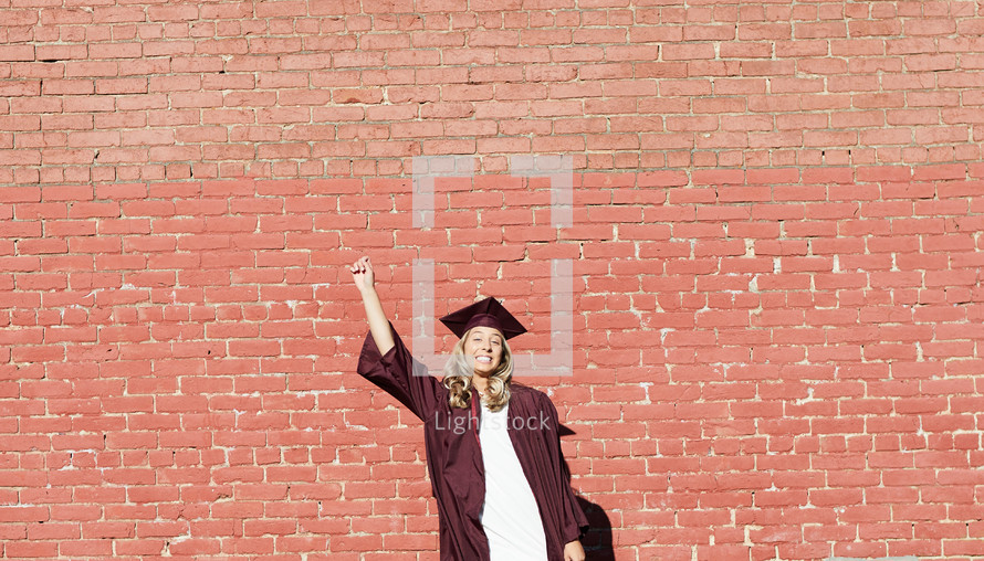 smiling female graduate standing in front of a brick wall
