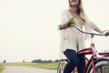 woman riding a bicycle holding flowers
