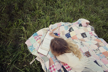 woman sitting outdoors reading a book lying on a blanket