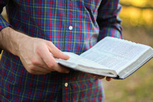 man standing holding a Bible