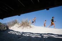boys running on a beach in summer