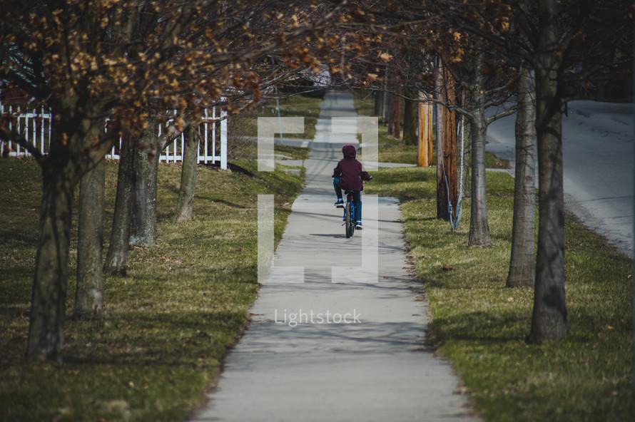 boy riding a bicycle on a sidewalk