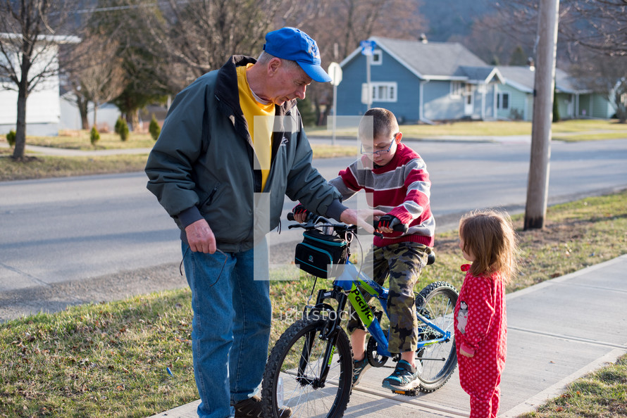 grandfather helping a boy ride a bicycle