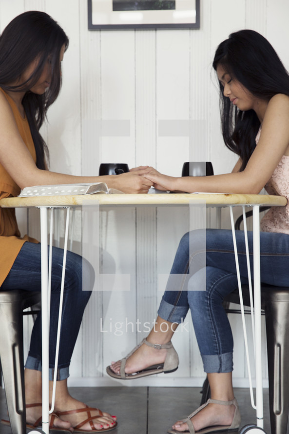 Two young women holding hands and praying together.