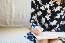 teen girl writing in a notebook
