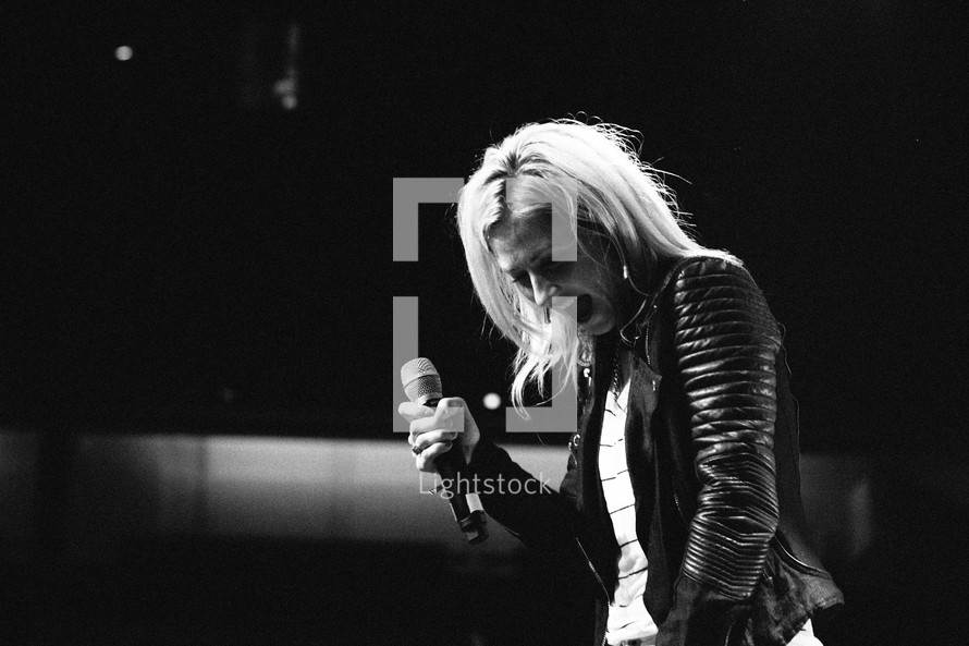 woman on stage with a microphone