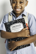 a boy child holding a composition notebook
