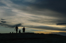 silhouettes of people on a mountain top