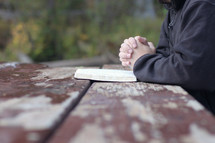 a man with praying hands over the page of a Bible