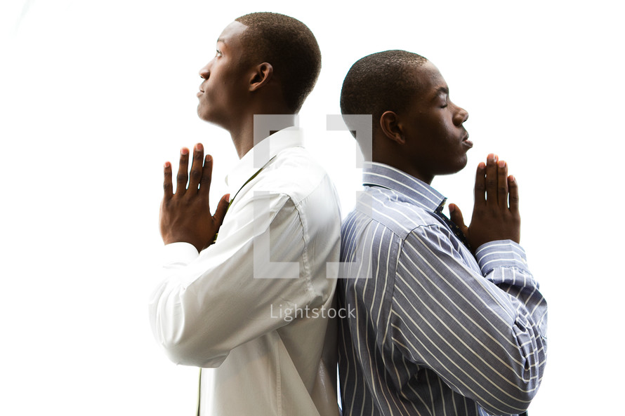 Two men standing back to back with praying hands.