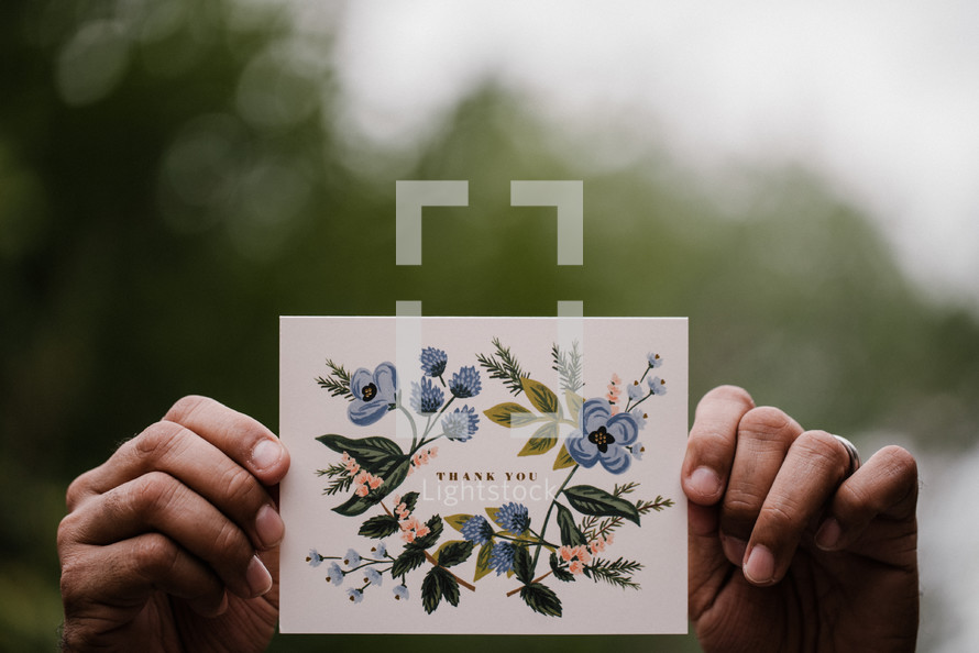 a man holding a thank you card