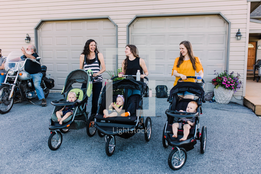 mothers standing together with babies in baby strollers