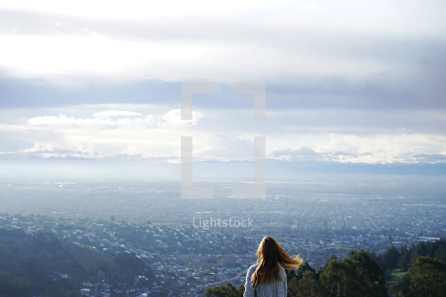 a woman looking out at the view of the suburbs