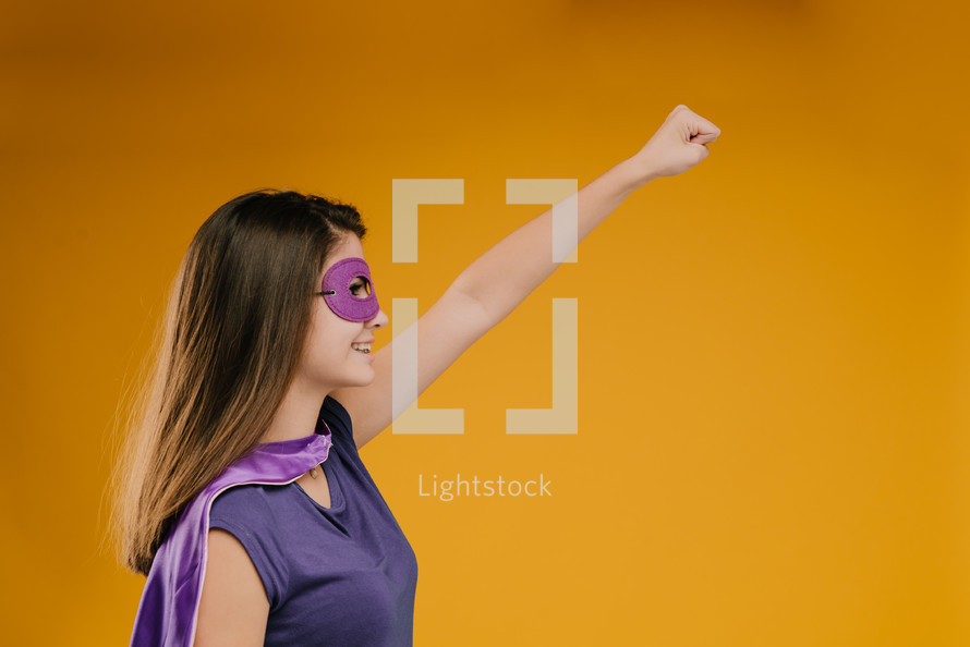 girl with a raised fist in a superhero costume