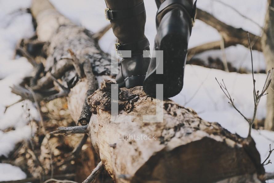 a woman in boots walking on a fallen tree log