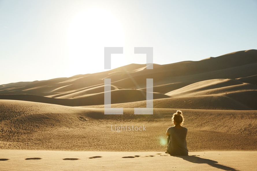 a woman sitting in a desert looking out at the view
