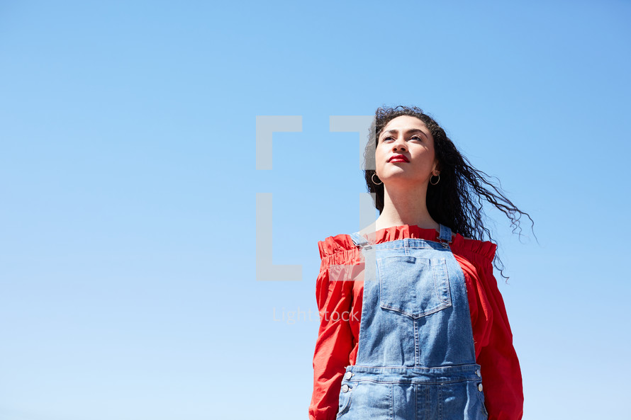 portrait of a woman standing outdoors against a blue sky