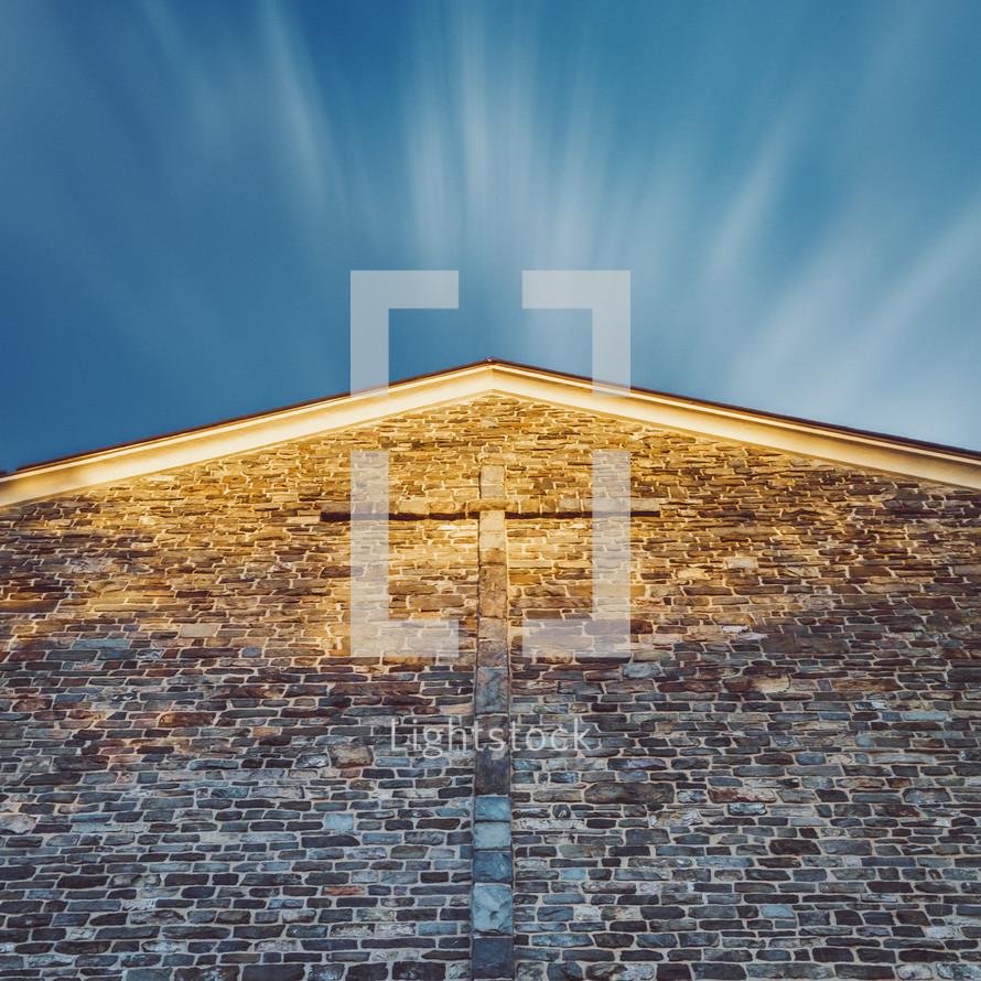 cross on a brick wall under a blue sky