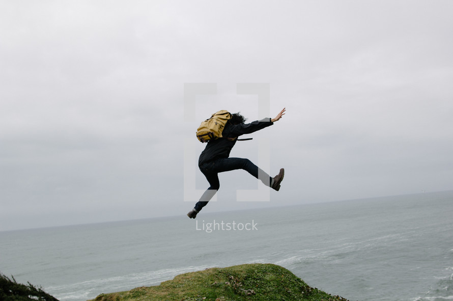 a man with a backpack leaping outdoors