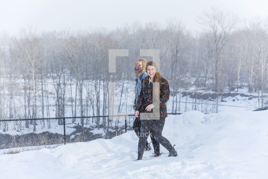two young adults out in snow having fun