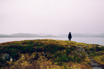 a woman standing on a grassy hill looking out at the water