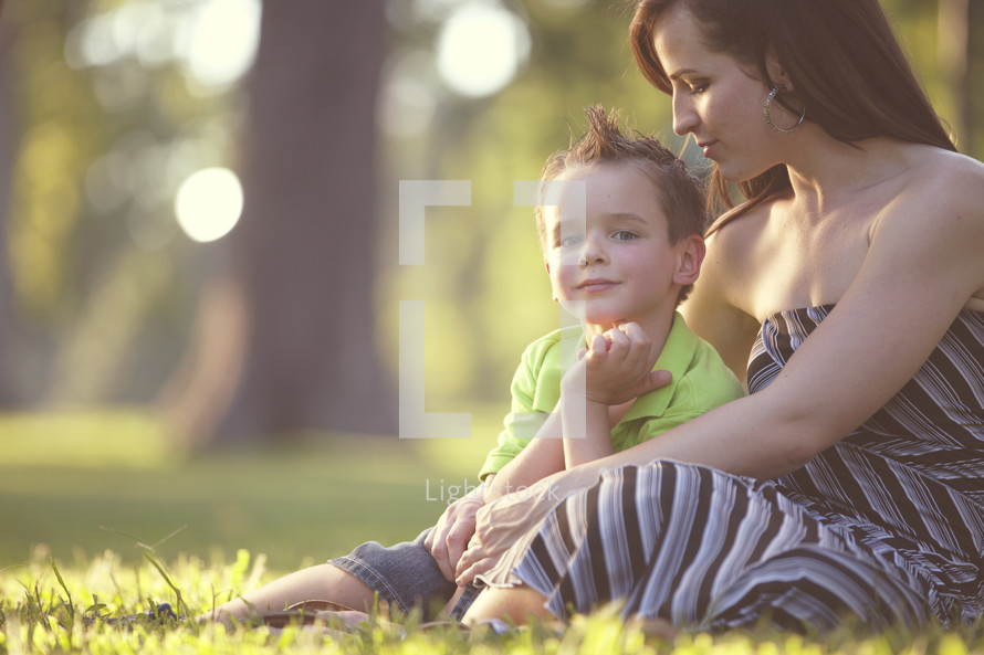 mother and son sitting in the grass