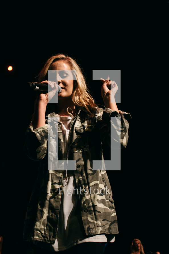 teen girl singing into a microphone