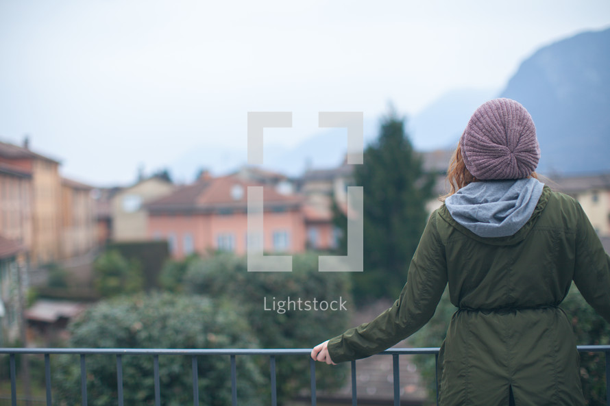woman standing at a railing looking out at a town