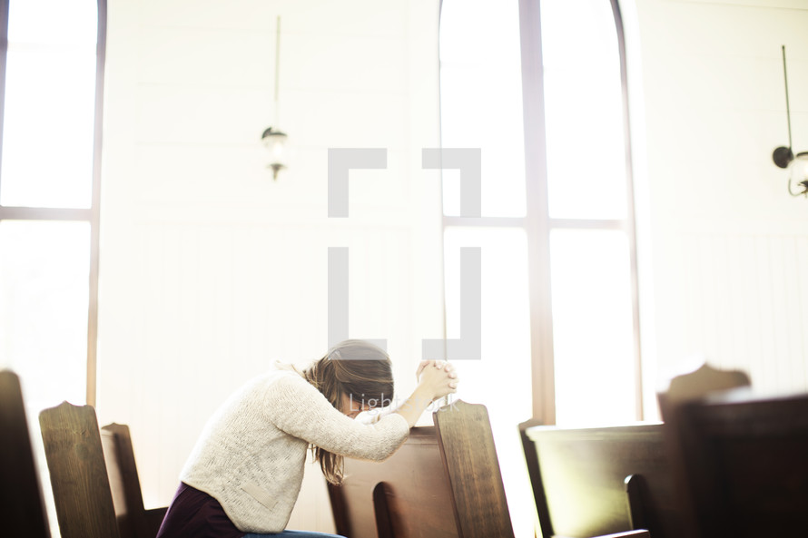 a woman praying in church pews