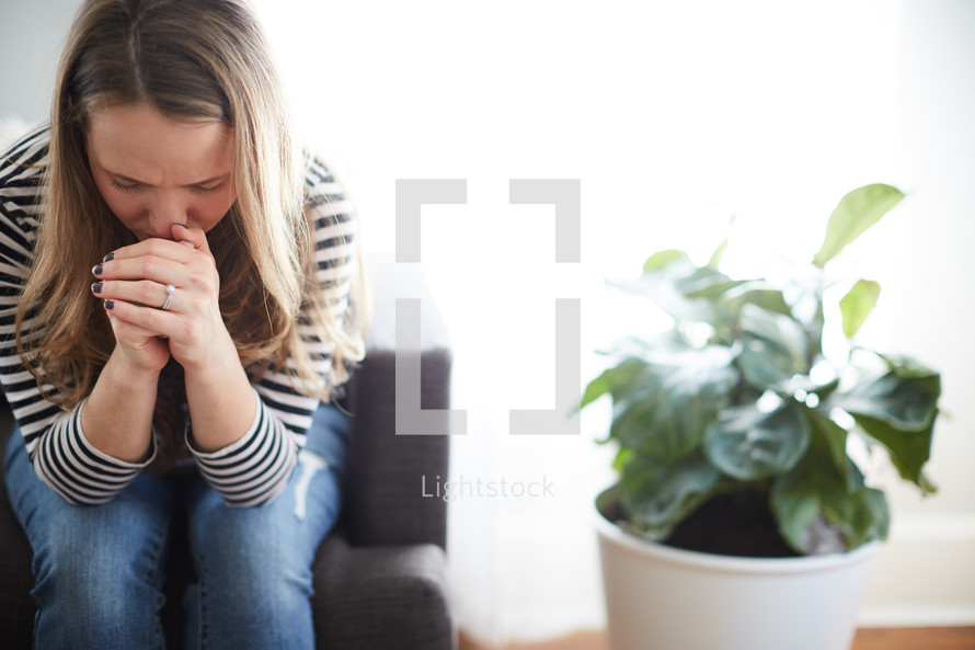 a woman sitting in a chair praying