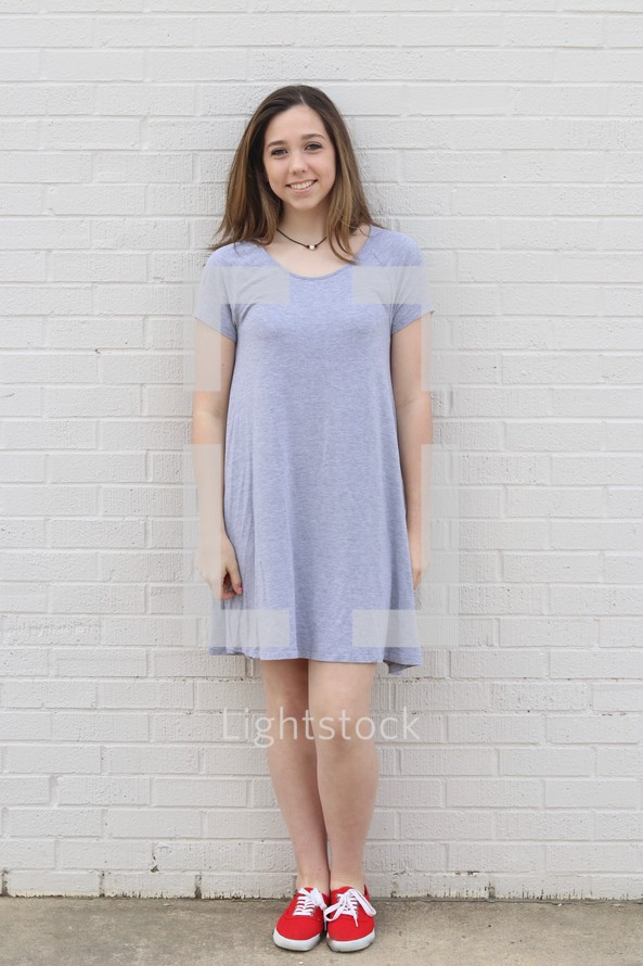 a teen girl standing in front of a white brick wall