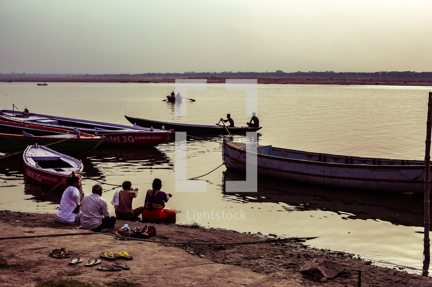 fishing boats and people sitting along a shore