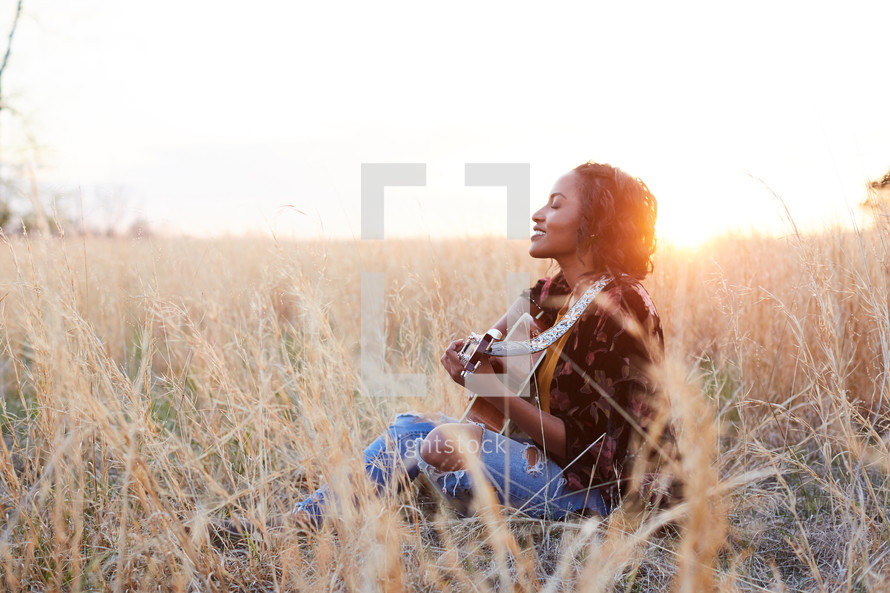 a woman sitting in a field with a guitar