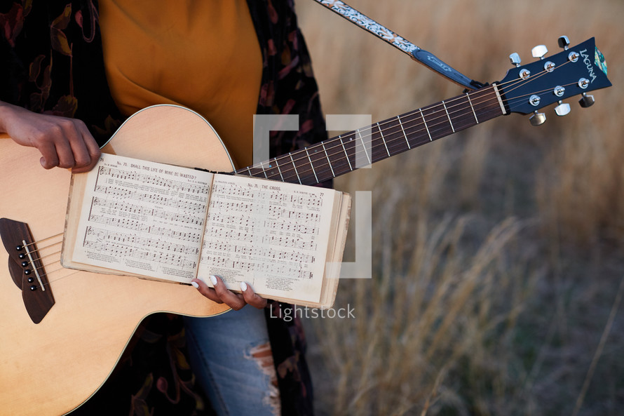 a woman standing in a field with a guitar and sheet music