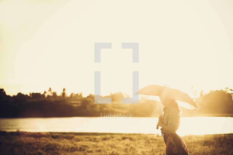 Woman walking by a lake at sunset.