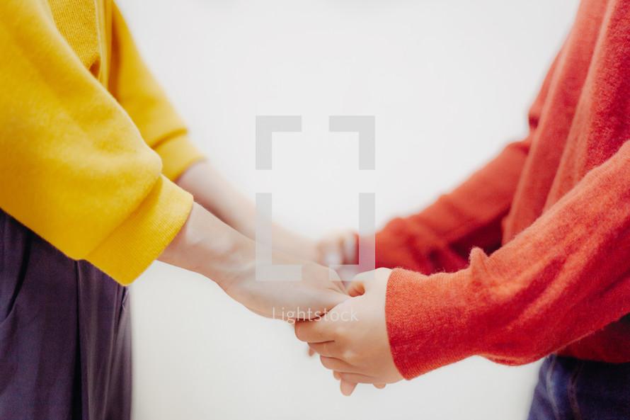a couple holding hands praying together